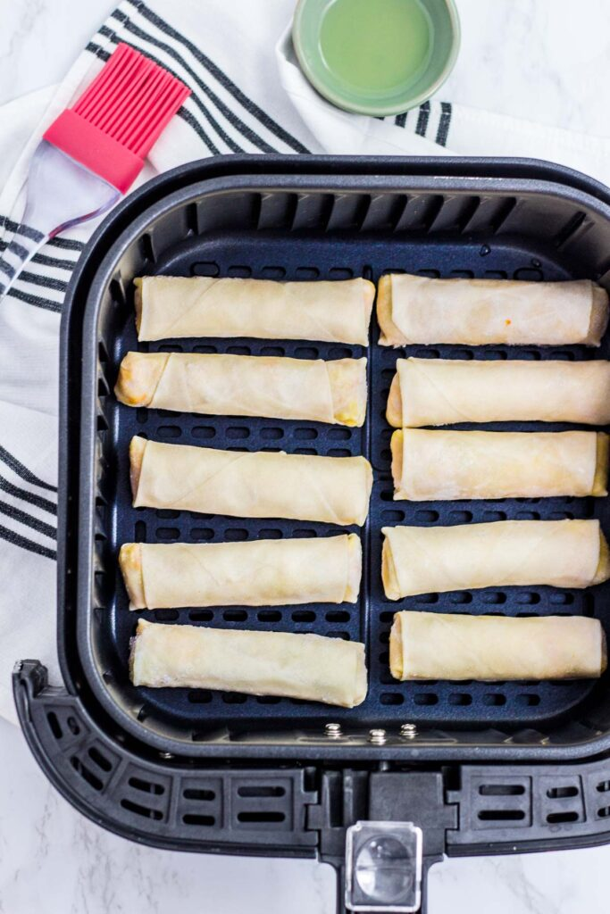 before picture of spring rolls in an air fryer basket
