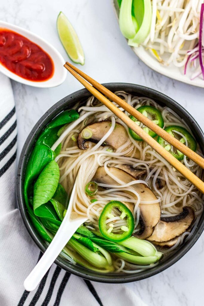 Vegan pho with mushroom, bok choy, and jalapeno in a large black bowl with sriracha sauce on the side