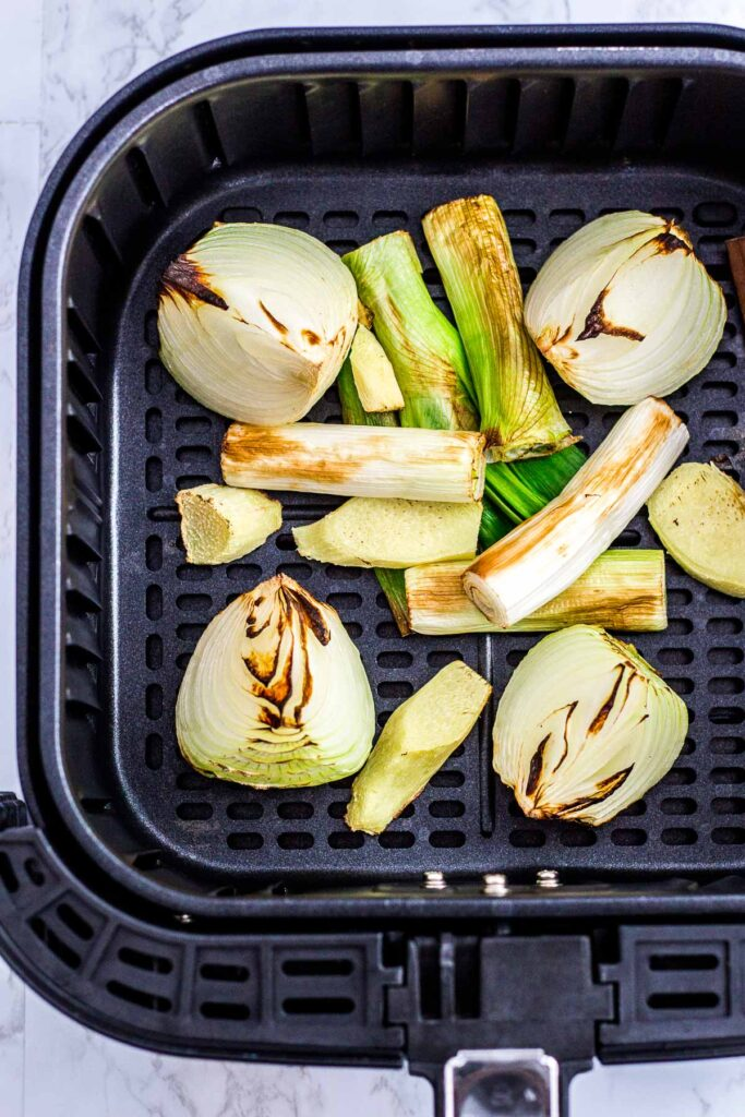charred onion, green onion, and ginger in an air fryer basket