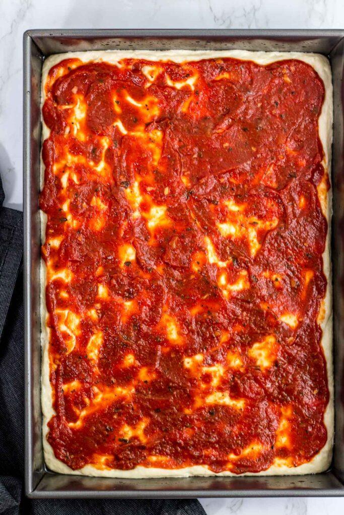 Pizza dough with sauce in rectangular pan