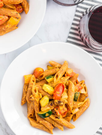two bowls of vegan creamy lentil pasta primavera with a glass of red wine in the background