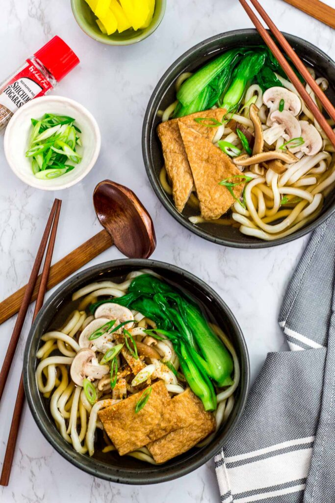 Overhead shot of two bowls of udon noodle soup