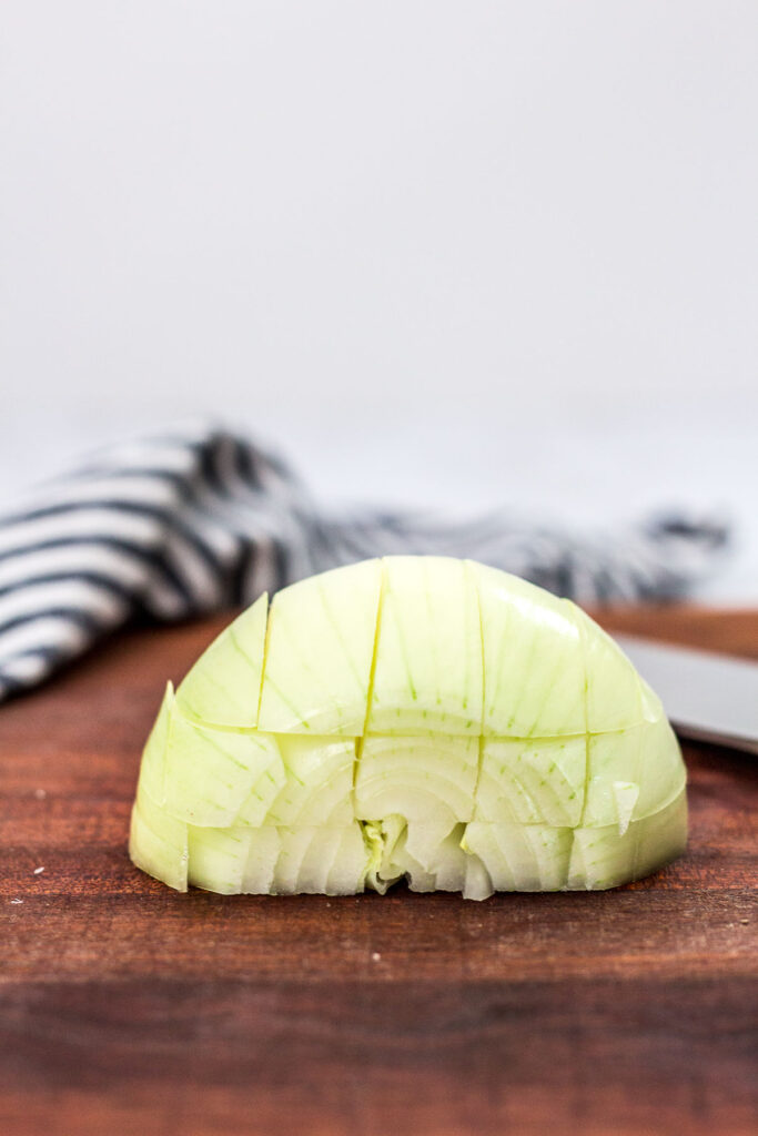 straight shot of half an onion sliced parallel and perpendicular to the cutting board