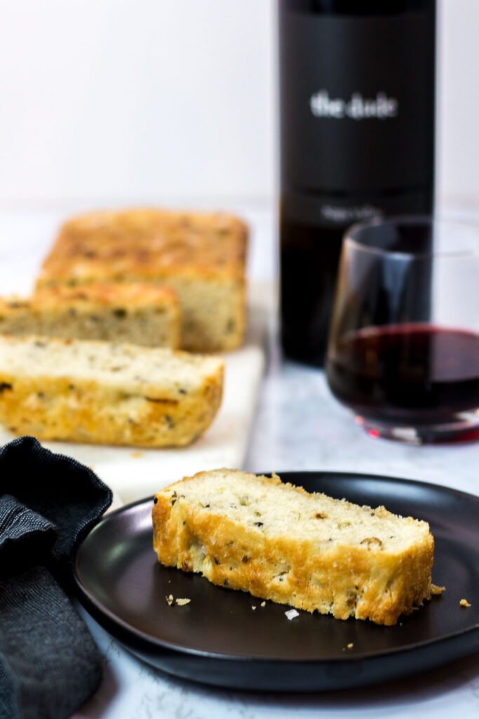 sliced small batch garlic green onion focaccia with a glass of red wine in the background