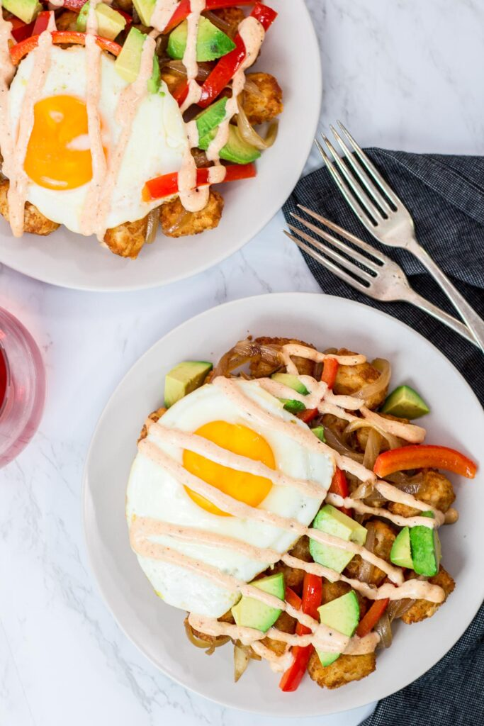 overhead shot of two plates of breakfast totchos