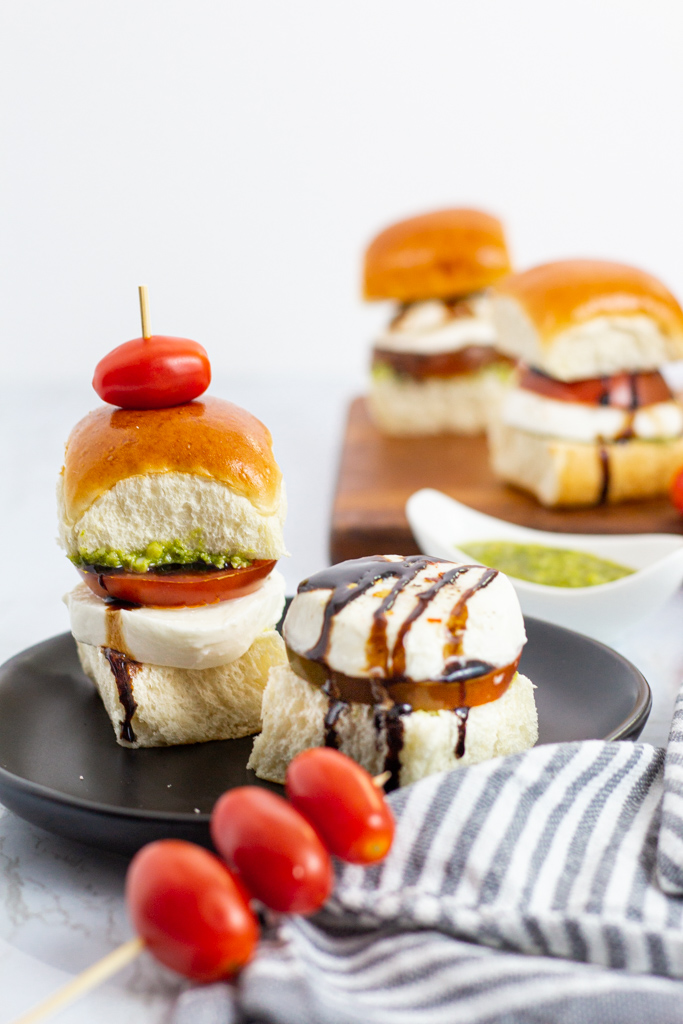 two caprese sliders on a plate and two more sliders in the background