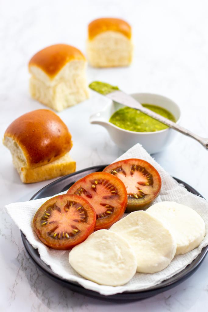 hawaiian buns, sliced tomato and fresh mozzarella cheese, and pesto