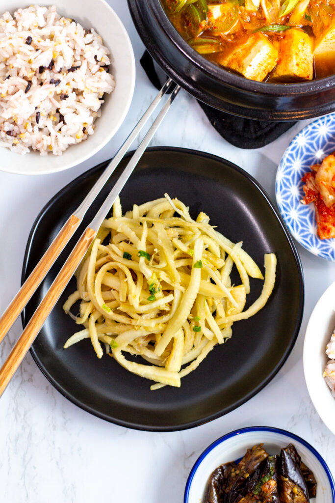 bellflower roots (doraji namul) with a bowl of rice and other Korean side dishes around it