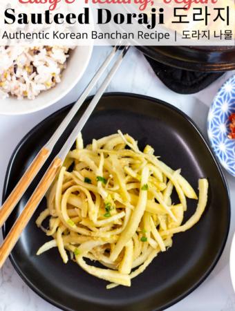sauteed doraji on a black plate with chopsticks next to it