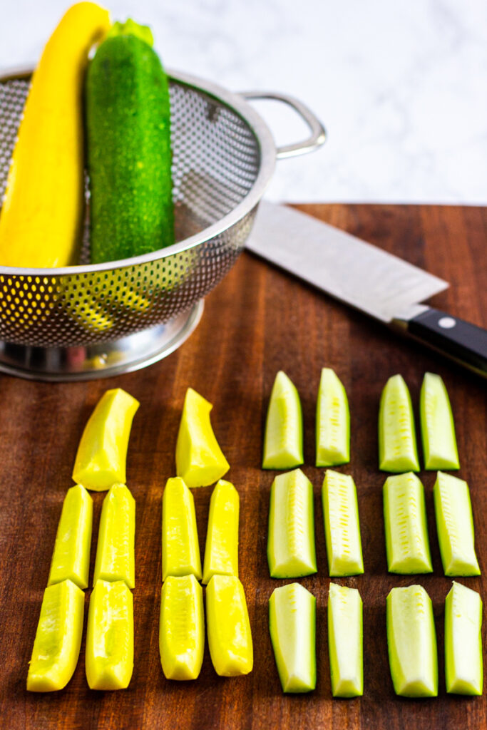 zucchini and yellow squash cut into 2-inch strips on a cutting board.