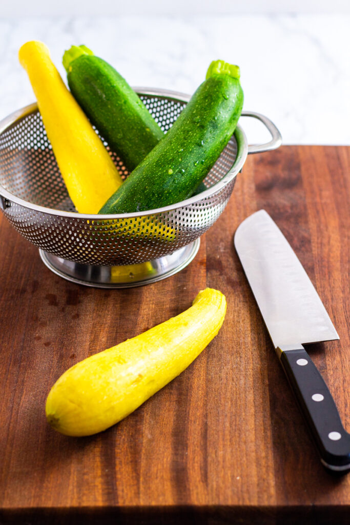 two washed zucchini and one yellow squash in a colander and one yellow squash on a cutting board.