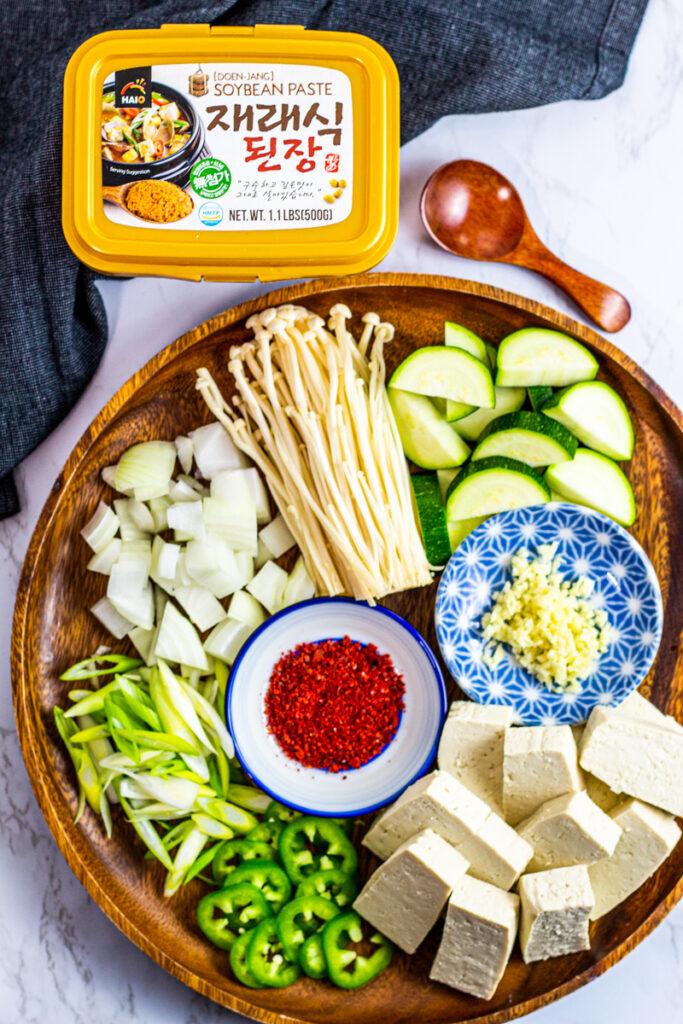 ingredients for the stew - zucchini, minced garlic, tofu, jalapeno, green onion, onion, gochugaru, enoki mushroom, and doenjang.