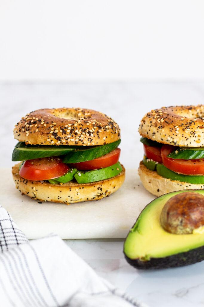 two avocado bagel sandwich on a white board.
