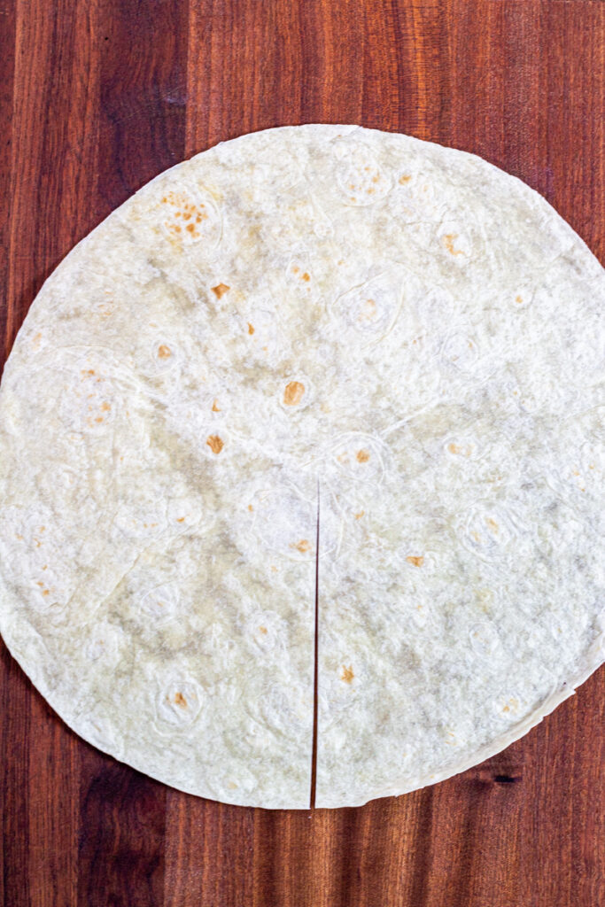 A large flour tortilla with a halfway cut from the center to the edge.