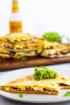 A piece of breakfast quesadilla with guacamole on top.