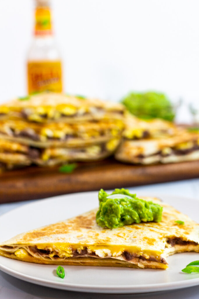 A piece of breakfast quesadilla with refried beans and eggs with a dollop of guacamole on top.