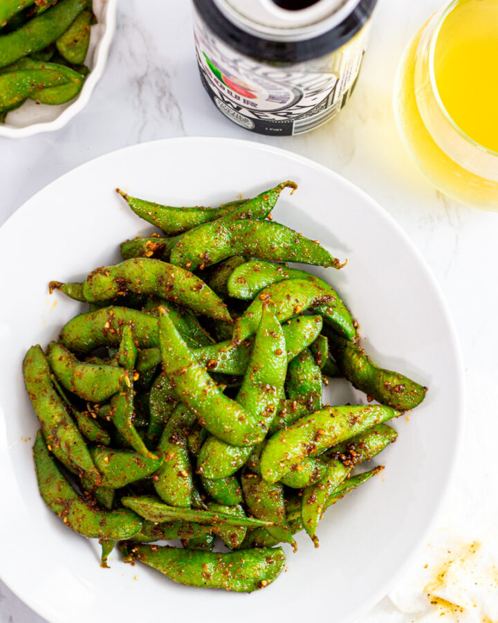 spicy edamame on a white plate with a glass of beer and the can next to it.