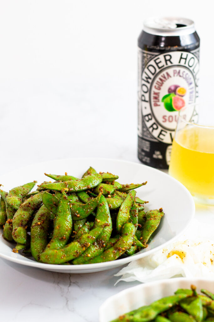 prepared edamame on a white plate with a glass of beer next to it.