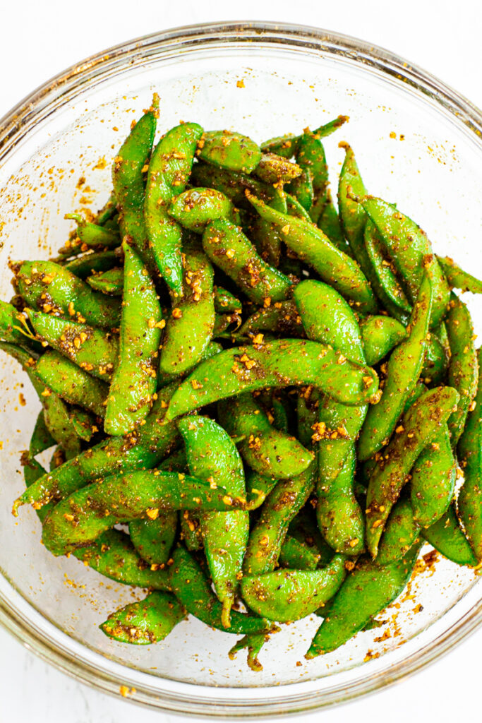 spicy edamame coated with seafood garlic butter in a clear bowl.