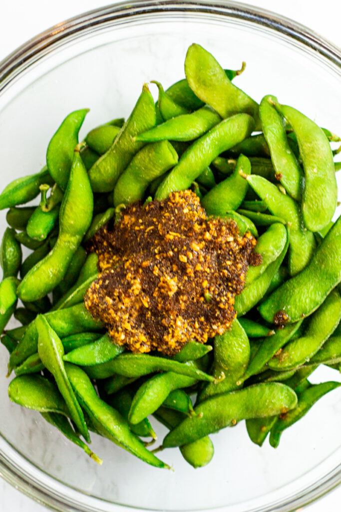 the seafood garlic butter sauce is poured over cooked edamame in a clear bowl.