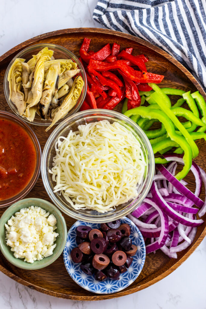 Toppings - roasted red bell pepper, fresh green bell pepper, red onion, olive, artichoke hearts, and cheese.