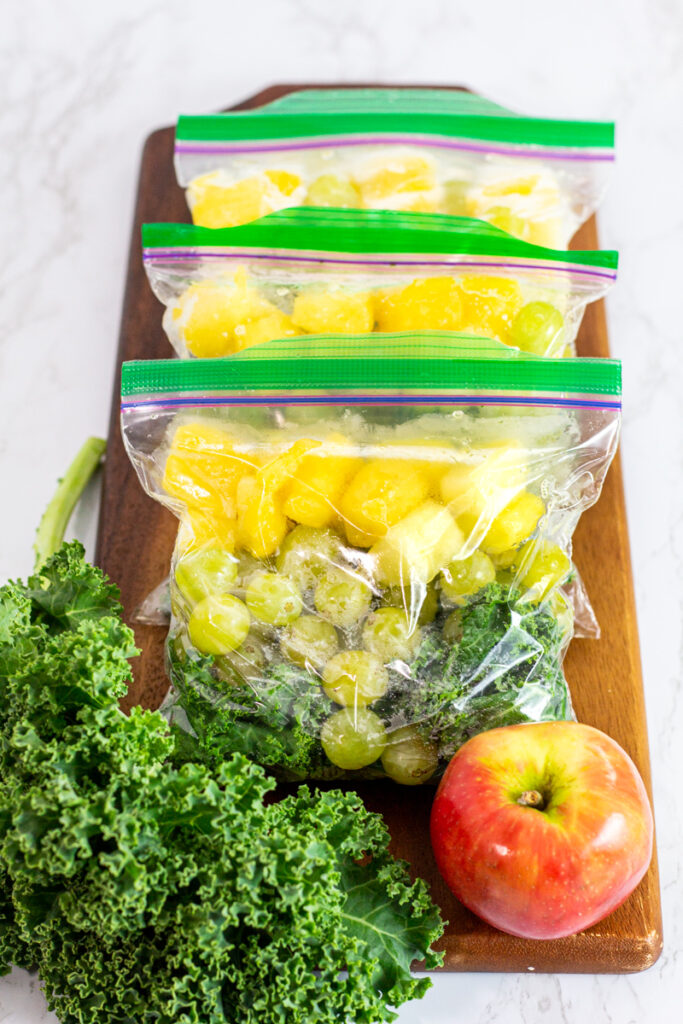 portioned out kale, grapes, and pineapple in freezer safe bags.