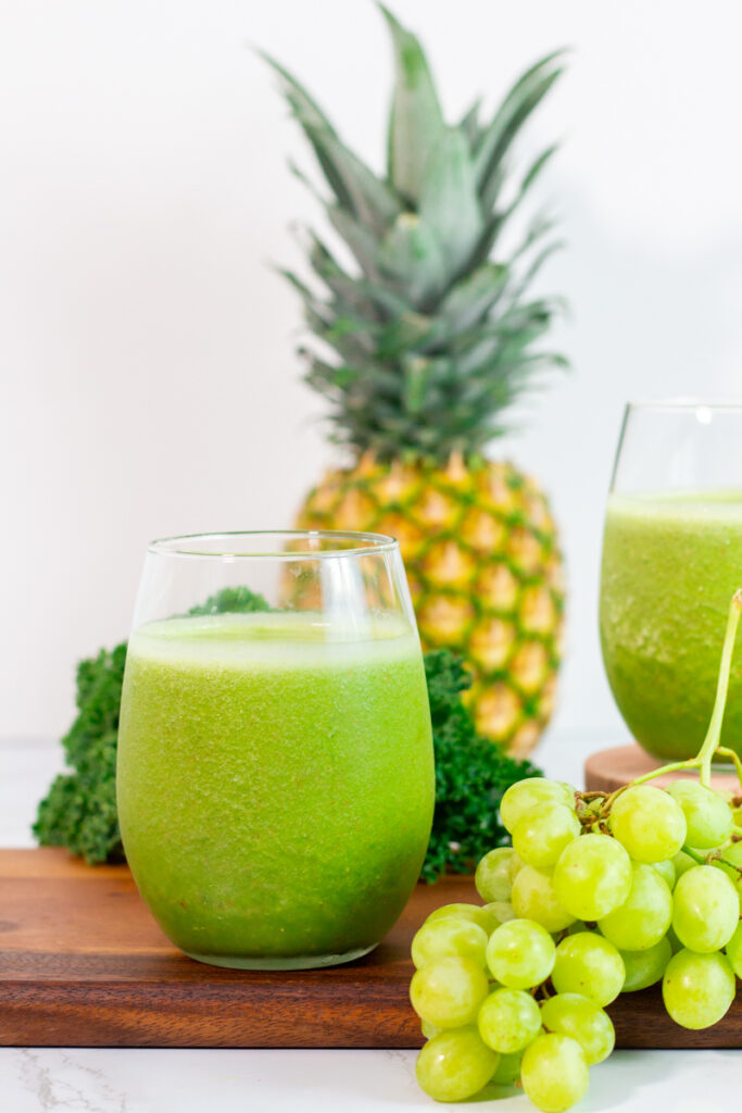 close up shot of green smoothie with kale, pineapple, and grape in the background.