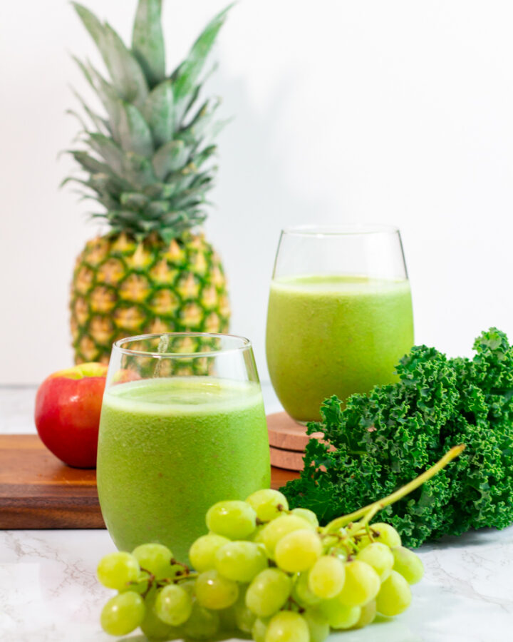two glasses of kale pineapple green smoothie with kale and fruits in the background.
