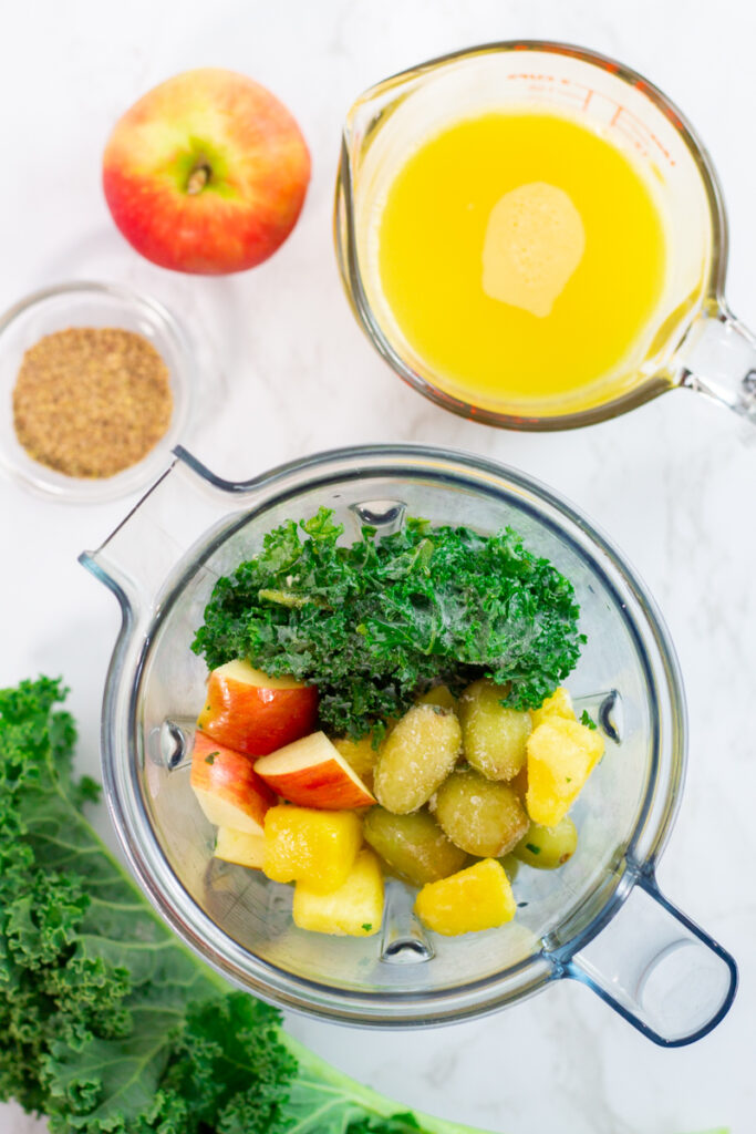 apple, frozen kale, grape, and pineapple in the blender with orange juice on the side.