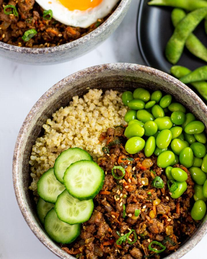 overhead shot of vegan buddha bowl with quinoa, vegan bulgogi, edamame, and cucumber slices.