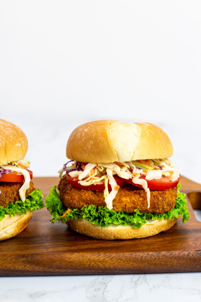 two vegan chicken sandwiches with pepper jelly coleslaw on a wooden board.