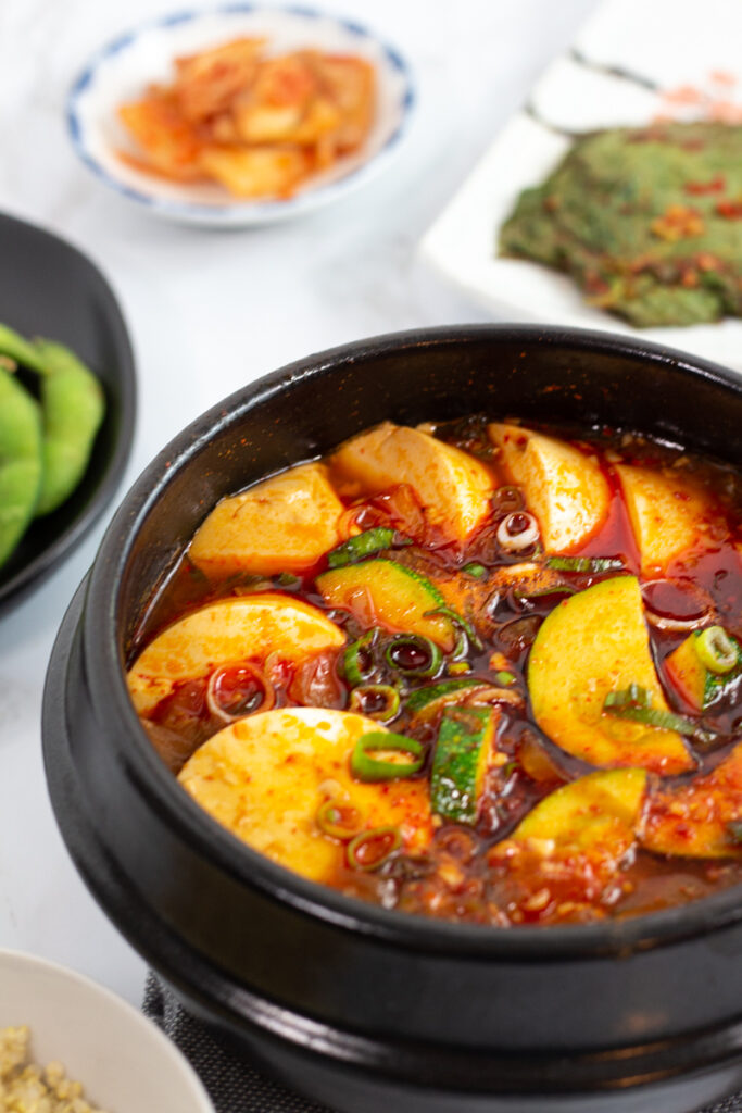 Vegan soondubu jjigae photo on an angle with other side dishes in the background.