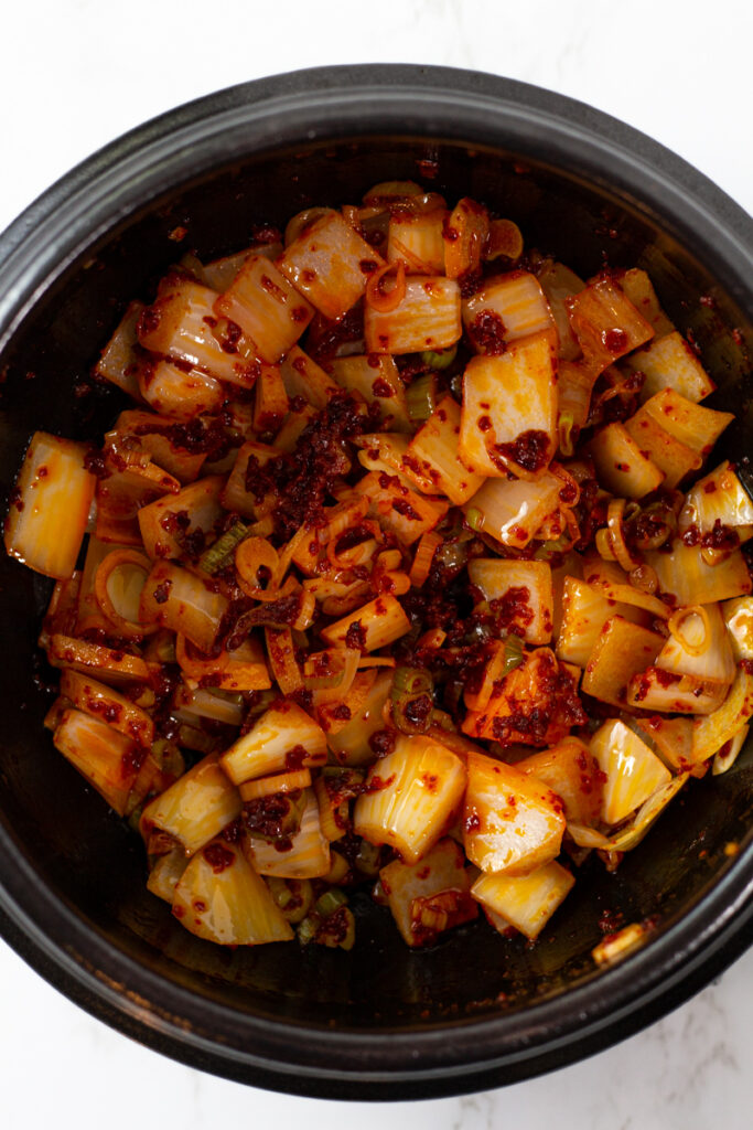 onion is added to the red pepper oil with green onion to the clay pot.